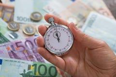 Dinero de Person Hands With Stopwatch Over Imagen de archivo