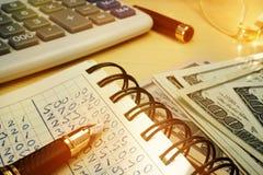 Dinero de presupuesto Libro con cálculos, la calculadora y los dólares fotografía de archivo libre de regalías
