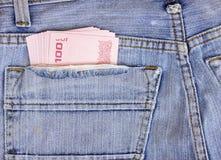 Dinero de Tailandia incluyendo el baht 100 en bolsillo trasero del blac de un hombre Imagenes de archivo