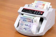 Dinero de Uzbekistán en una máquina de cuenta fotos de archivo