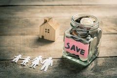 Dinero del ahorro de la familia para la casa de compra Fotos de archivo libres de regalías