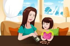 Dinero del ahorro de la madre y de la hija a una hucha Imágenes de archivo libres de regalías