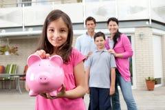 Dinero del ahorro de la muchacha con la familia en la parte posterior Foto de archivo