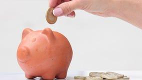 Dinero del ahorro de la mujer en una arcilla tradicional b guarro almacen de metraje de vídeo