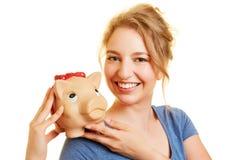 Dinero del ahorro de la mujer joven con la hucha Foto de archivo libre de regalías