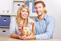 Dinero del ahorro de los pares con la hucha Imagen de archivo