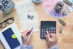 Dinero del ahorro y concepto de las finanzas, mujer que usa una calculadora y plumas de tenencia en la tabla, tono del color del  fotos de archivo
