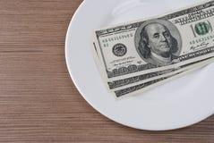 Dinero del billete de banco del dólar en la placa blanca Imagenes de archivo