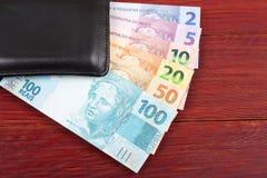 Dinero del Brasil en la cartera negra Foto de archivo libre de regalías