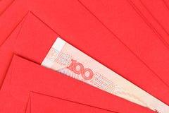 Dinero del chino o de 100 billetes de banco de Yuan en sobre rojo, como chino Imagen de archivo libre de regalías