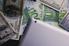 Dinero del dólar y del euro, tableta, cierre del teléfono celular para arriba foto de archivo libre de regalías