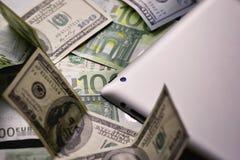 Dinero del dólar y del euro, tableta, cierre del teléfono celular para arriba imagenes de archivo