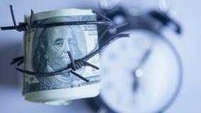 Dinero del d?lar americano envuelto en alambre de p?as contra fondo del reloj imágenes de archivo libres de regalías