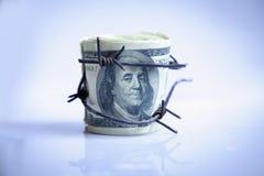 Dinero del d?lar de EE. UU. envuelto en alambre de p?as como s?mbolo de la guerra econ?mica imagen de archivo libre de regalías