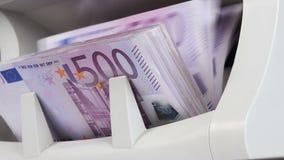 Dinero del efectivo que cuenta la máquina El contador del billete de banco está contando quinientos cuentas euro almacen de video