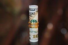 Dinero del rollo de los billetes de dólar con joyería del oro Fotos de archivo