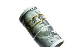 Dinero del rollo de los billetes de dólar con la cadena del oro Foto de archivo libre de regalías