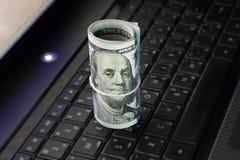 Dinero del rollo de los billetes de dólar en el teclado del ordenador portátil Imagen de archivo libre de regalías