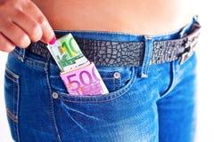 Dinero en bolsillo delantero de los pantalones vaqueros de las muchachas Foto de archivo
