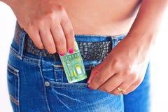 Dinero en bolsillo delantero de los pantalones vaqueros de las muchachas Fotos de archivo libres de regalías