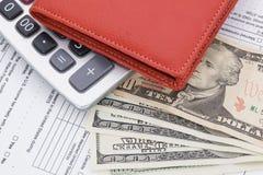 Dinero en cartera y calculadora en fondo de la forma de impuesto imagenes de archivo