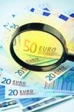 Dinero en circulación euro bajo una lupa imagenes de archivo