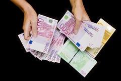 Dinero en circulación euro en manos en negro Imagen de archivo libre de regalías