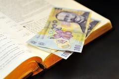 Dinero en circulación rumano de ofrecimiento y biblia santa Imagen de archivo