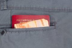Dinero en el bolsillo trasero de sus pantalones Imagenes de archivo