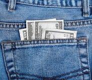Dinero en el bolsillo trasero de vaqueros Foto de archivo libre de regalías