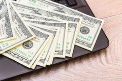 Dinero en el teclado de ordenador en fondo de madera Imagenes de archivo