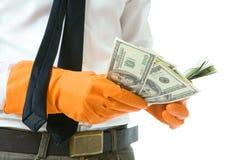 Dinero en guantes de goma anaranjados Foto de archivo libre de regalías