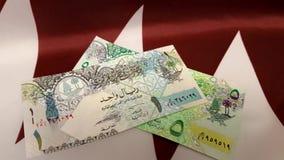 Dinero en la bandera de Qatar almacen de metraje de vídeo