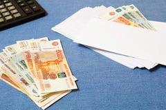 Dinero en la pila y el sobre con las cuentas Imagen de archivo