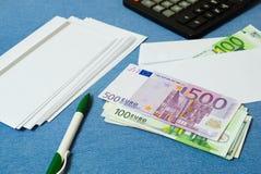 Dinero en la pila y el sobre con las cuentas El sueldo en un sobre Fotos de archivo