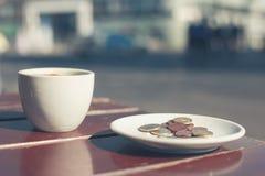 Dinero en la tabla del café Foto de archivo