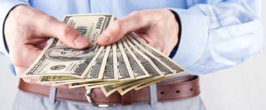 Dinero en las manos del hombre de negocios fotos de archivo