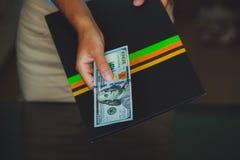 Dinero en las manos humanas, mujeres que dan dólares Imagen de archivo libre de regalías