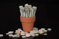 Dinero en pote de la terracota con los botones Fotografía de archivo libre de regalías