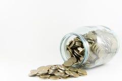 Dinero en un tarro de cristal en un fondo blanco fotografía de archivo libre de regalías