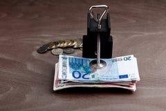 Dinero en una abrazadera con un humor oscuro Fotos de archivo