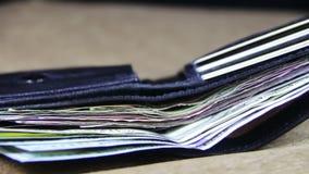 Dinero en una cartera que gira en una tabla de madera almacen de metraje de vídeo