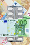 Dinero enfermo con las píldoras Imagenes de archivo