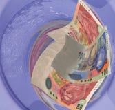 Dinero enrasado abajo del dren del tocador Fotos de archivo libres de regalías