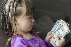 Dinero, finanzas y concepto de la gente - la niña sonriente con el dólar cobra el dinero fotografía de archivo