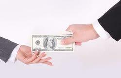 Dinero gaiving del hombre de negocios a la mano de la mujer Foto de archivo