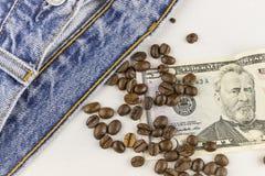 Dinero, granos de café y vaqueros Foto de archivo libre de regalías