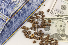 Dinero, granos de café y vaqueros Imagen de archivo