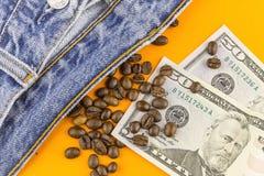 Dinero, granos de café y vaqueros Foto de archivo