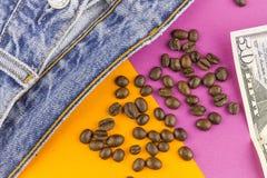Dinero, granos de café y vaqueros Imagenes de archivo